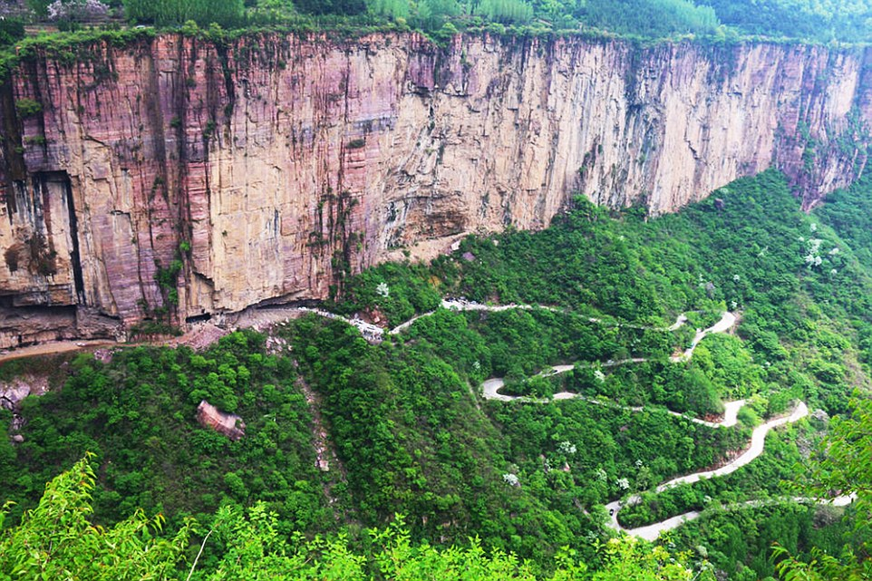 "Pic shows: Tourists in the cliff-side road during May Day holidays. Hundreds of tourists found themselves stranded in traffic on a cliff-side motorway leading to one of the country's most remote villages during the three-day May Day holidays. Some visitors had packed onto tour buses while others drove their own vehicles to reach the Taihang Mountains in central China's Henan Province, where the solitary mountain road offers access to the remote Guoliang Village. With few places that traffic can pass, it meant the narrow road quickly became gridlocked with vehicles unable to go up, or down. The road, completed almost four decades ago, still remains the only way in and out of the village, which has now become one of the country's must-see destinations for photographers hoping to capture a dramatic view. However, the road was not always meant for tourism. Before the construction of the road, residents accessed the village via a steep staircase known as the ""sky ladder"", or ""tianti"" in Chinese, named for its elevation and narrowness. But after village elders decided that they wanted to connect with the ""outside world"", and also make easier for those who wished to visit, construction began in 1972 for what would eventually become one of the country's most spectacular driveable roads. The 3m-wide, 4.5m-high, single-lane road was carved out on the side of the canyon by 13 strong villagers, who completed the feat in just five years for a grand opening in 1977. The mile-long road is now wide enough for modern-day vehicles to pass through side-by-side, but it means traffic is slow. Alternatively, visitors can hike up the road instead to reach Guoliang Village, which is known for being built entirely out of stone. (ends)"